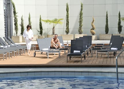 Couple relaxing on loungers by the pool